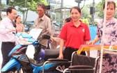 第五郡郡委書記阮文孝(左)向家境困難民戶轉交摩托車以作謀生工具。