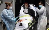 圖為紐約的一名新冠肺炎女患者獲送上救護車。(圖源:路透社)