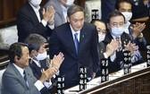 日本首相菅義偉向全體與會者鞠躬行禮,以示敬意。(圖源:共同社)