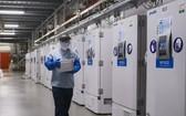醫護人員在冷藏設備處拿取疫苗。(圖源:路透社)