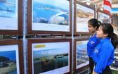 """年輕人參觀了解""""越南的黃沙與長沙群島-歷史證據與法理依據""""地圖與資料展。(圖源:鄧俊)"""