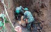 2名工兵將戰後遺留的老炸彈搬移現場。(圖源:英好)