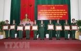 國防部長吳春歷大將(中)向越南人民軍國防部、總參謀部、總政治部領導授予三等軍功勳章。(圖源:越通社)