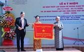 市各友好組織聯合會王德煌軍(左)向市越南-古巴友好協會代表贈送市人委會傳統錦旗。(圖源:明協)