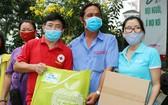 第五郡紅十字會主席黎勛峰(左)與「Habitat」項目管理人胡氏梅英(右)向貧困戶贈送禮物。