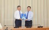 新任市教育與培訓廳副廳長楊智勇(左)從市人委會副主席楊英德手中接過人事委任《決定》。(圖源:孟和)