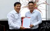 《西貢解放報》執行副總編輯阮玉英(左)向文忠孝同志頒授任命書。