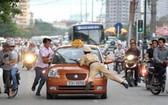 一名違規的計程車司機不但不遵守交警的號令,而且還直接朝交警的方向撞過來,交警措手不及,只好撲到車上的前蓋。