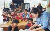 《西貢解放報》副總編輯李越中向廣義省茶林小學生贈送書本。