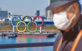 一名戴口罩的男子在奧運五環背景中行走。(圖源:AP)