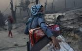 9月9日,希臘萊斯博斯島的莫里亞難民營發生大火後,一位移民帶著自己的物品離開難民營。(圖源:路透社)