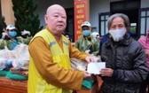 釋惟鎮法師向貧困者派發救濟品。