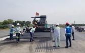 工人們在途徑前江省州城縣申九義鄉的路段進行舖築瀝青混凝土。(圖源:TTO)