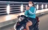 女騎士不但放手騎車,還在高速中揮舞雙手模仿扇子舞姿態,模樣相當危險。(圖源:視頻截圖)