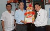 曾友鋒同志(右一)向華人老幹部朱杞文贈送新年禮物。