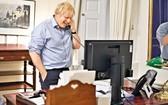 英國首相約翰遜23日和美國總統拜登通電話時笑逐顏開。(圖源:路透社)