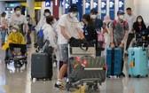 """疫情期間""""全副武裝""""的乘客在機場準備登機。(圖源:互聯網)"""