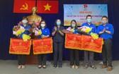郡人民議會主席黃玉女芳紅(左三)、共青團第五郡郡委書記黎雄勇(右一)向各領先單位贈送錦旗。