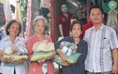 富山五行廟慈善組組長鄒國榮(右一)向貧困者派發賑濟品。