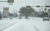 2月15日,在美國得克薩斯州休斯敦,車輛在積雪的道路上行駛。(圖源:新華社)
