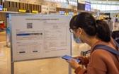 乘客在雲屯機場做電子健康申報。(圖源:D.Ngoc)