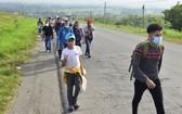 1月15日,在洪都拉斯北部城市科夫拉迪亞,中美洲民眾在當地公路上向北行進,希望能夠經由墨西哥進入美國。(圖源:新華社)