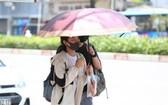 一對情侶撑著伞走在烈光下。(圖源:越通社)