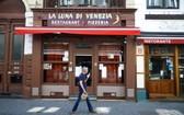 2020年5月30日,在比利時布魯塞爾,一名男子經過一家關閉的餐館。 (圖源:新華社)