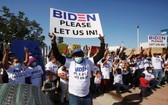 來自中美洲和其他民族的移民在美墨邊境附近聚集並高舉標語,籲拜登讓他們進入美國。(圖源:路透社)