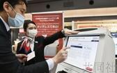 日本航空公司22日在東京羽田機場第一航站樓,推出了不直接用手碰觸觸控面板屏幕也可操作的值機設備和自動行李托運設備。(圖源:共同社)