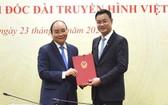 新任越南電視台總經理黎玉光(右)從阮春福總理手中接過人事委任《決定》。(圖源:陳海)