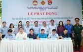 第五郡越南祖國陣線委員會副主席陳南德(右三前排)與第三、六、八、十、十四坊人委會簽署備忘錄。