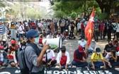 3月27日,緬甸仰光淡汶鎮抗議民眾佔領一條街道同軍警對峙。 (圖源:AP)