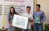 華人畫家羅漢榮(中)向崑崙島博物館代表贈送畫作。