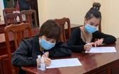 被查獲的兩名非法入境者在填寫醫療申報。(圖源:前鋒)