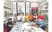 張漢明老師(右起第五位)讓學生實習畫作。