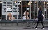一名女子走過法國巴黎街頭一家關門的餐館。(圖源:新華社)