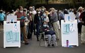 民眾在加州迪士尼樂園度假區接種疫苗的地點排長隊等候。(圖源:路透社)