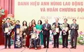 國家主席阮春福(右四)與榮獲革新時期勞動英雄稱號的代表及家屬合照。(圖源:越通社)