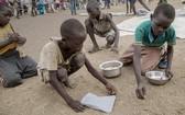 在烏干達的一個難民營帳區,南蘇丹孩子把派發糧食時掉在地上的榖物逐粒拾起來。(圖源:互聯網)