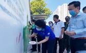 市越南祖國陣線委員會主席蘇氏碧珠與各代表一同塗鴉宣傳壁畫。(圖源:市越南祖國陣線委員會)
