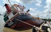 Alica號貨輪在靠岸拋錨時突發傾斜,導致大量集裝箱墜落河中。(圖源:越通社)