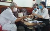 社保公務員親自上門為退休者支付退休金。(圖源:T.N)