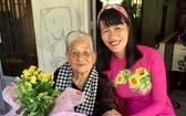 阮氏明心帶著學生的鮮花和信探望越南英雄母親陳氏近。