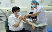 醫護人員為衛生部長阮清隆(左)注射新冠疫苗。(圖源:越通社)