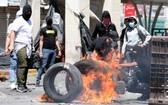 巴勒斯坦人在衝突中點燃了橡膠輪胎。(圖源:EPA)