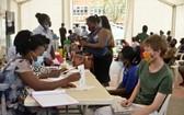 5月21日,人們在烏干達坎帕拉接種新冠疫苗前登記信息。(圖源:新華社)