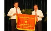 市人委會主席阮成鋒(右)向取得本市2020年競賽運動出色成績的單位頒發競賽錦旗。