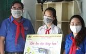 值市少年先鋒隊成立80週年,市共青團副書記吳明海向清貧隊員贈送學習角。