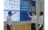 市電力總公司(EVNHCMC)理事會主席范國寶(中)考察市電力數據 中心管理室。